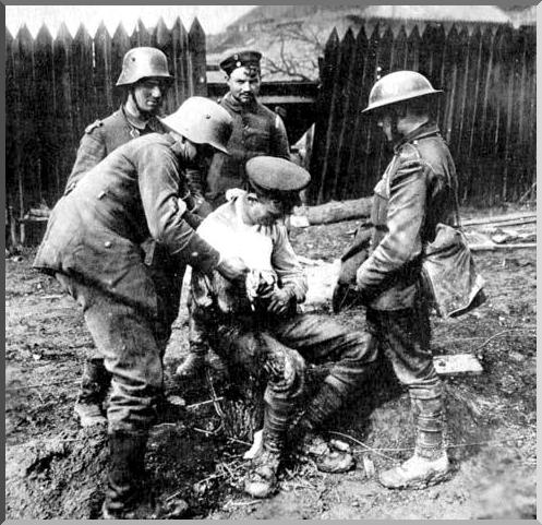 German soldiers dressing a wounded British soldier's wounds